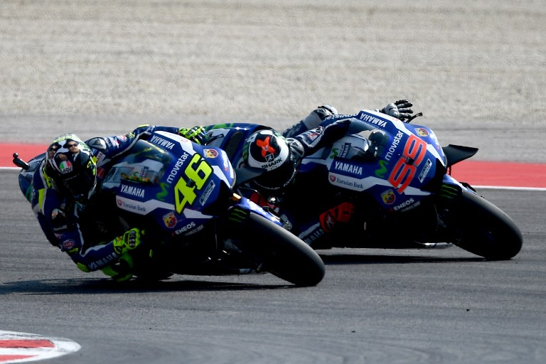 Movistar Yamaha MotoGP's Italian rider Valentino Rossi (46) outpasses Movistar Yamaha MotoGP's Spanish rider Jorge Lorenzo (R) during the San Marino Moto GP Grand Prix race at the Marco Simoncelli Circuit in Misano, on September 11, 2016. / AFP PHOTO / GABRIEL BOUYS